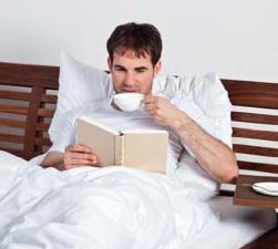 Mann lesend im Bett